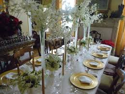 Centerpiece For Table by White Flowers On The High Glass Vase Combined With Golden Plates