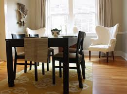 white armchairs closed window and dark brown dining set on nice