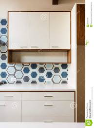 Mid Century Modern Window Trim by White Kitchen Cabinet In Modern Home With Blue Tile Royalty Free