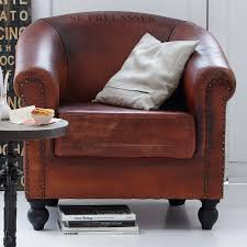 brown leather reading chair with rustic accent pillow and round