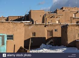 a resident clears snow from the roof of an old adobe home at the a resident clears snow from the roof of an old adobe home at the ancient native american taos pueblo outside taos new mexico the pueblos are considered to