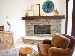 grey stone fireplace with brown wooden mantel shelf and white