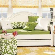 traditional wooden daybed with trundle bed and white bedding