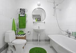 bathroom white bathtub white toilet white wall round mirror green