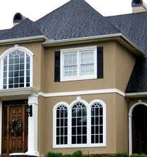large home painted with 3 colors tan stucco cream trim and black