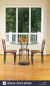 vertical photo of small dining room with red oak floors glass