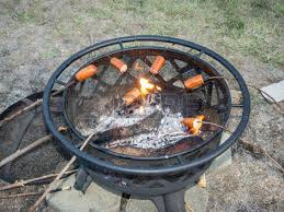 Cooking Over Fire Pit Grill - roasting sausages on wooden sticks over a fire pit stock photo