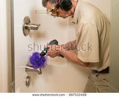 senior working man cleaning shower bath stock photo 667532476