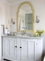 this traditional white bathroom features a gold trim mirror