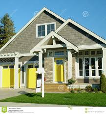 exterior of yellow house with blue garage door and asphalt