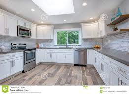 white kitchen cabinets with stainless steel backsplash open concept kitchen equipped with stainless steel