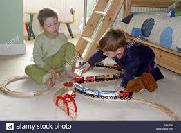 two young boys playing with train set and toys in their bedroom