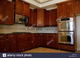 oak kitchen cabinets with stainless steel appliances kitchen cabinets with stainless steel appliances stock photo