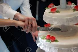 bride and groom cutting the wedding cake together with knife stock