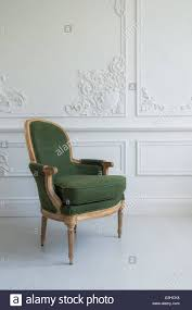 one classic armchair against a white wall and floor copy space