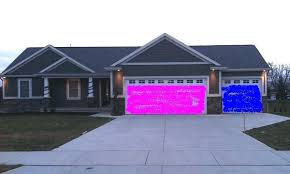 a periwinkle two story house has garage doors one painted lime
