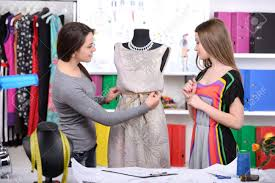 fashion designers at work two cheerful young women working at