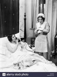 1920s 1930s two women in bedroom maid looking at wrist watch other 1920s 1930s two women in bedroom maid looking at wrist watch other woman in bed talking on phone hand held over mouthpiece