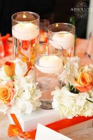 Centerpieces With Candles For Wedding Receptions by Tall Vases With Floating Candles Embellished With White Hydrangea