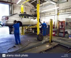 2 car mechanics working in a repair garage with hydraulic liftcar