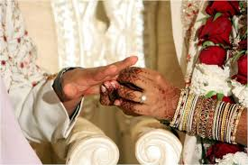 indian wedding band groom slips wedding band on beautiful s finger during