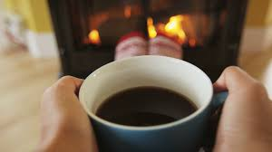 woman drinking coffee by fireplace getting warm and cozy person