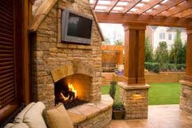 outdoor stacked stone fireplace with tv mount with attached