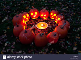carved pumpkins in a circle at twilight around a pumpkin pie on