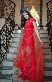 the beautiful in a long red dress posing in a vintage scene