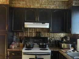 distressed black kitchen cabinets with metal backsplash timeles