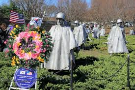 memorial wreaths and flags near statues of soldiers standing in