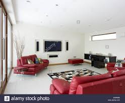 modern living room with red leather sofas and built in plasma tv