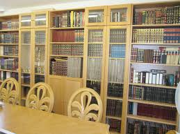 large white wooden bookshelves with glass doors and drawers placed
