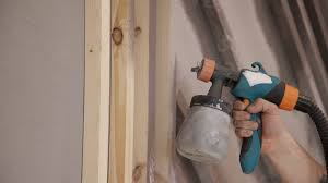 Room Painter Close Up Of Worker Hand Using Spray Gun And Painting Wood In House