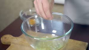 Organic Kitchen Utensils - egg yolk falling in glass bowl baking ingredients separating the