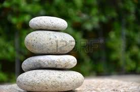 stack of zen rocks in garden on green background stock photo