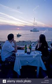 couple has romantic dinner at sunset dinning in the greek island