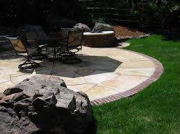 Flagstone Patio Installation Cost by Buff Flagstone Patio With Brick Edge And Natural Boulders By