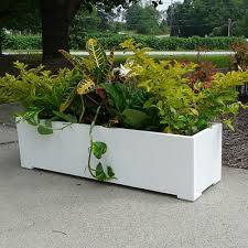 white plastic outdoor planter with tropical plants window boxes
