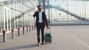 stylish young bearded man talking on the phone while entering the stylish young bearded man in sunglasses exiting the airport terminal with luggage talking on the