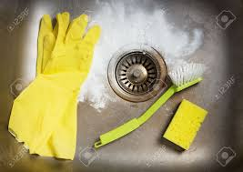 Cleaning Kitchen Sink by Cleaning Products And Rubber Gloves In A Dirty Kitchen Sink Stock
