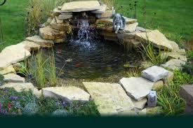 small backyard koi pond design with stone border and waterfall