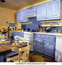 Yellow Kitchen Table And Chairs - stock photograph of paint effect distressed blue fitted cupboards