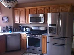 i like this look a lot black appliances cherry cabinets and i