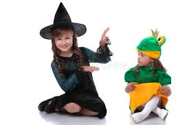 cute sisters posing in costumes of witch and frog stock photo