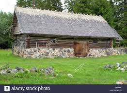 old farm house with straw roof and stone fundament stock photo