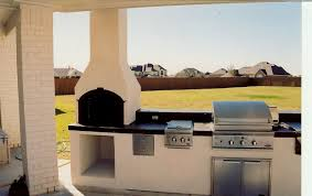 fetching outdoor kitchen with fireplace featuring stainless steel
