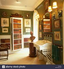classical bust on circular cupboard in green bathroom with stock
