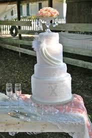 pale pink vintage wedding cake with draping spanish lace monogram