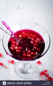 pomegranate martini pomegranate martini with pomegranate seeds in a glass on a white